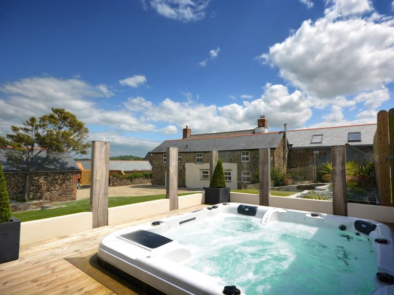 Relax in the sunken hot tub with views across the garden to the house