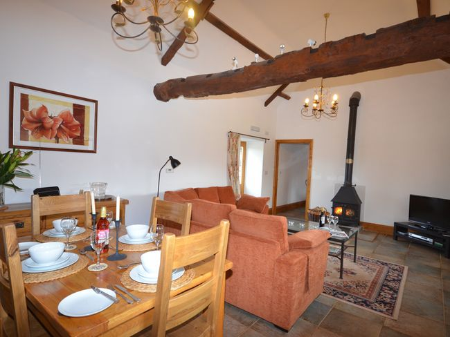 Lounge/dining area with woodburner, high ceilings and exposed beams