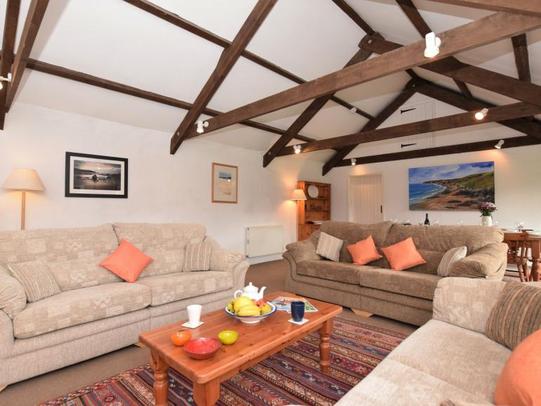 Large lounge/diner with high ceilings, exposed beams and a woodburner