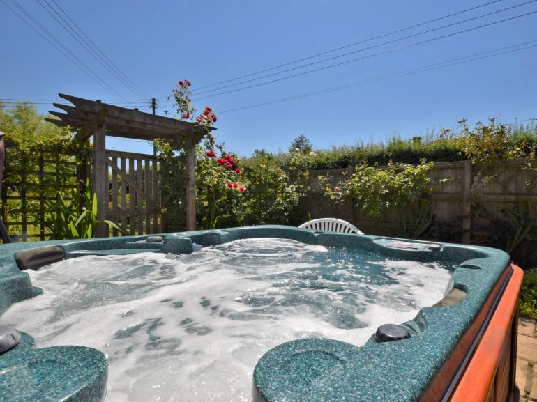 Relax in the enclosed hot tub area beside the garden