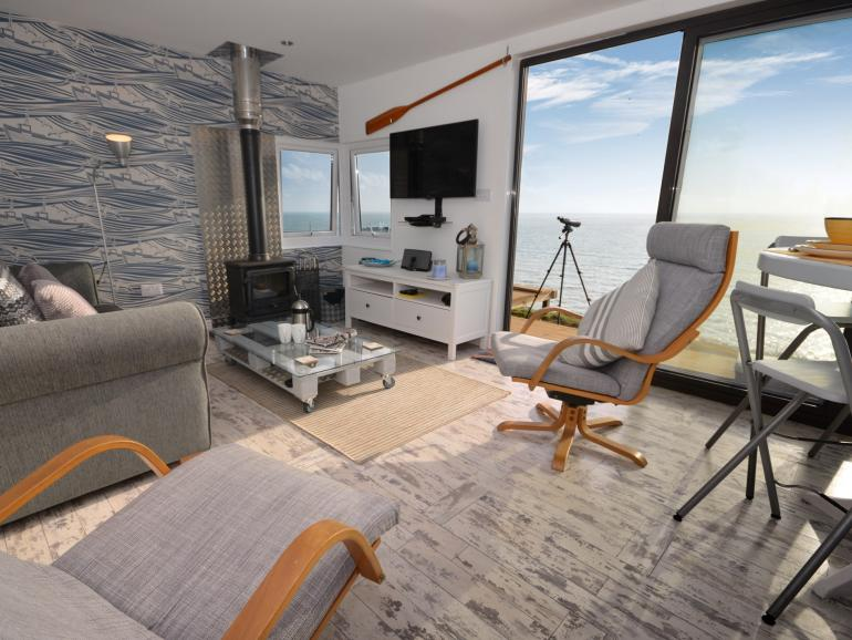 Lounge with woodburner and panoramic sea views