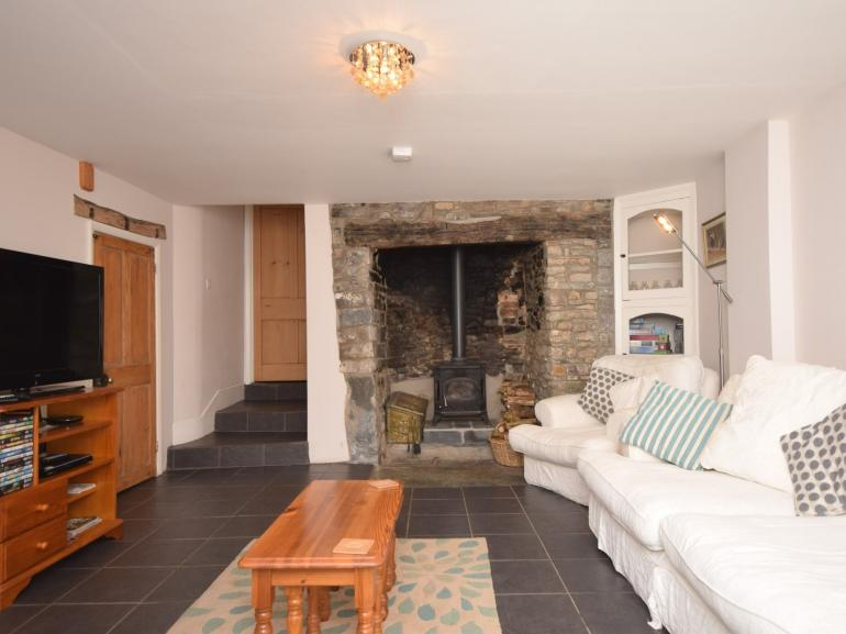 Lounge with woodburner and steps to kitchen
