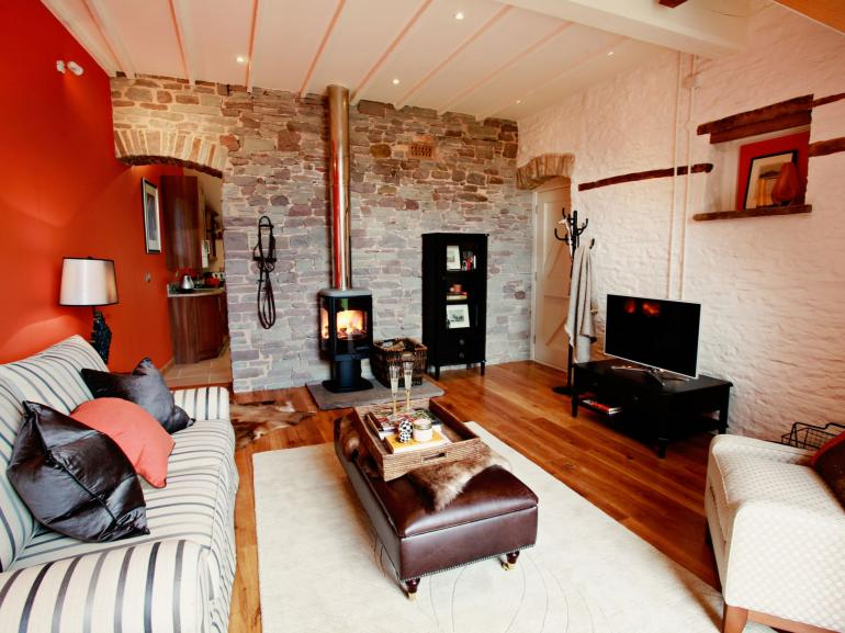 High ceilings, warming wood burner and huge glass doors, sit back and relax in style