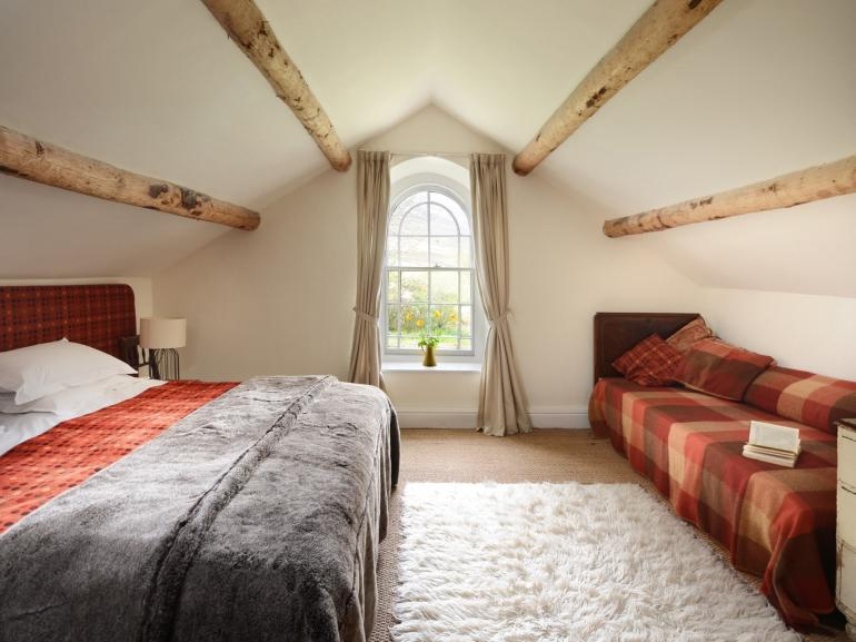 The bedroom is complete with sumptuous bedding and throws