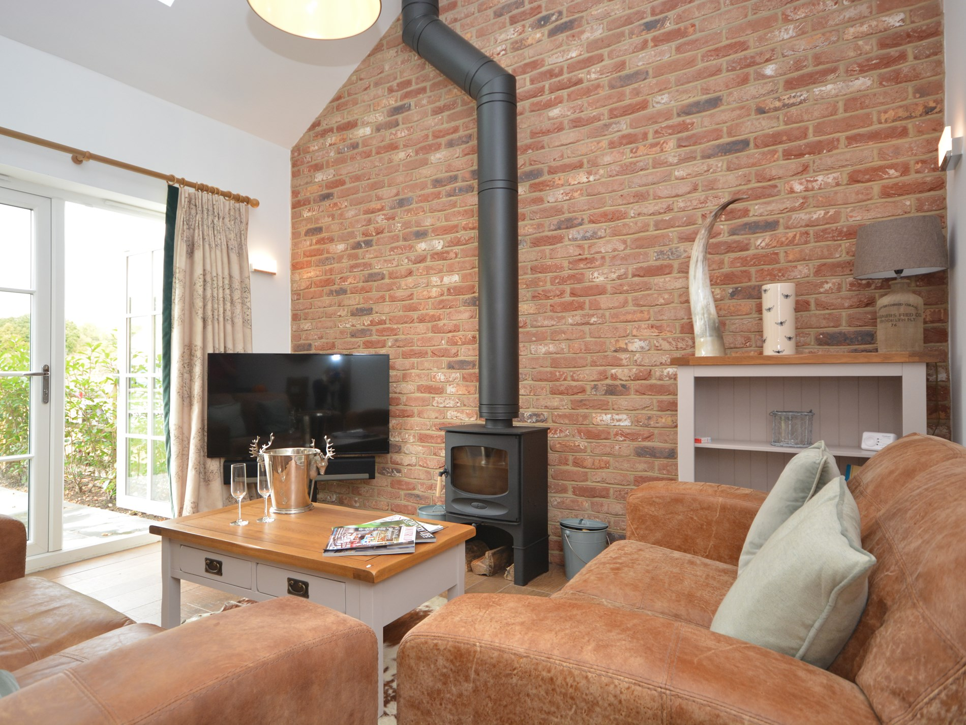 Cosy lounge area with woodburner and doors into garden