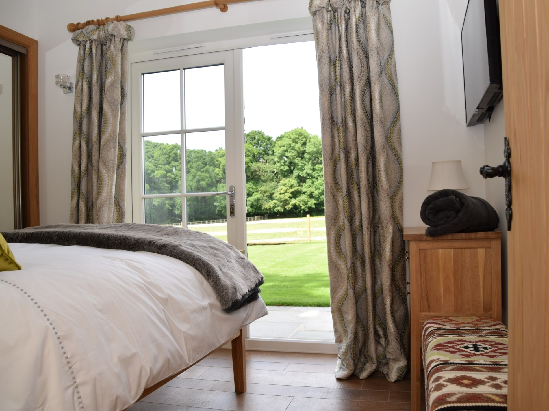 Bedroom with doors leading to lawn area