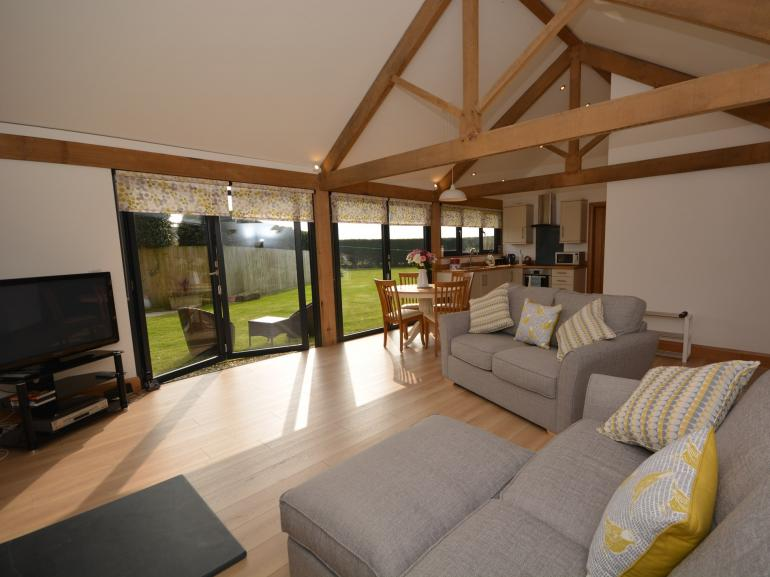 Bright open plan living space with feature beams