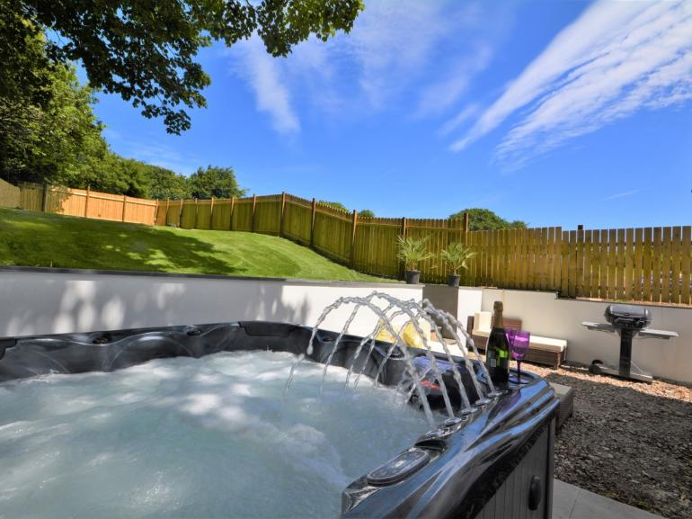 Enclosed rear garden with hot tub and patio with seating