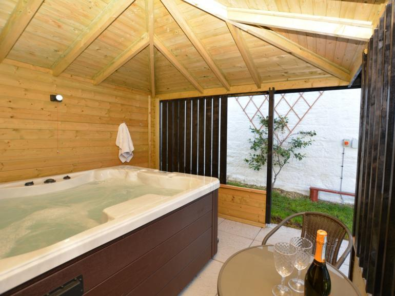 Private housed hot tub with seating area