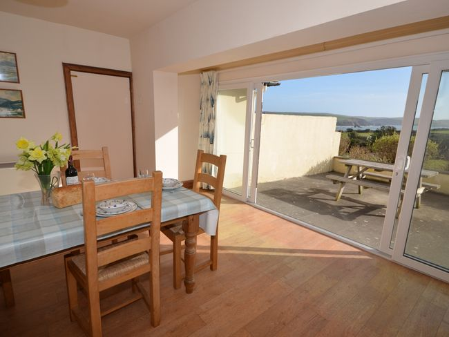 Dining area with patio doors and sea views