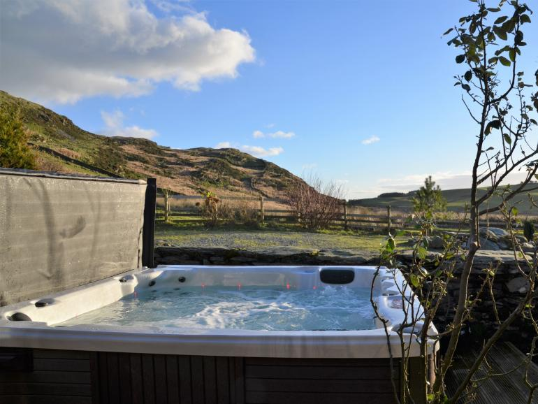 Relax in the hot tub, set in peaceful and private surroundings