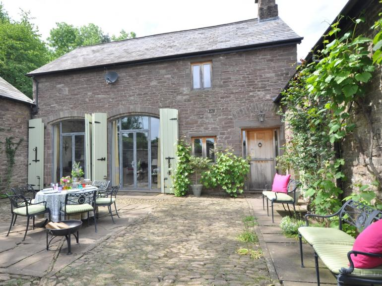 Traditional stone coach house set in a gated courtyard