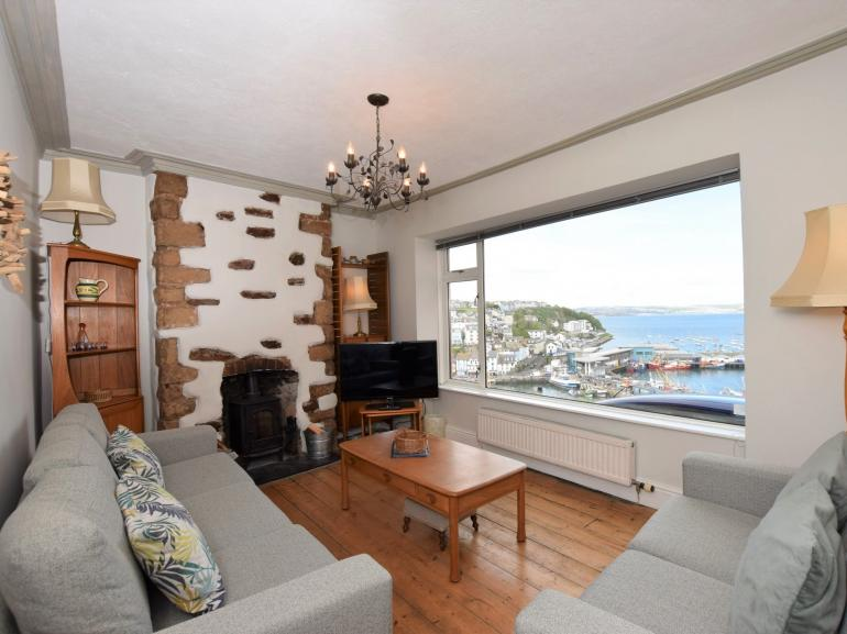 Lounge with original stone chimney breast and amazing harbour views