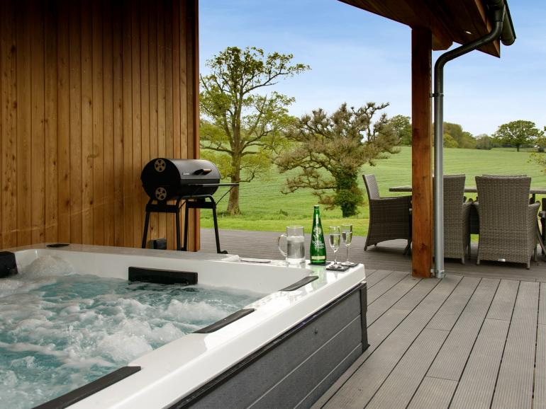 Relax in the private hot tub while soaking up the stunning rural views