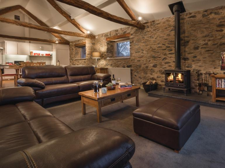 Spacious lounge with exposed stone wall and woodburner
