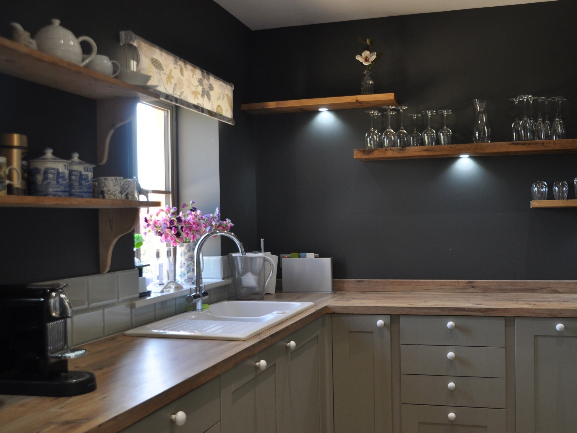 The hand crafted shelving enhances the style of this well-equipped kitchen