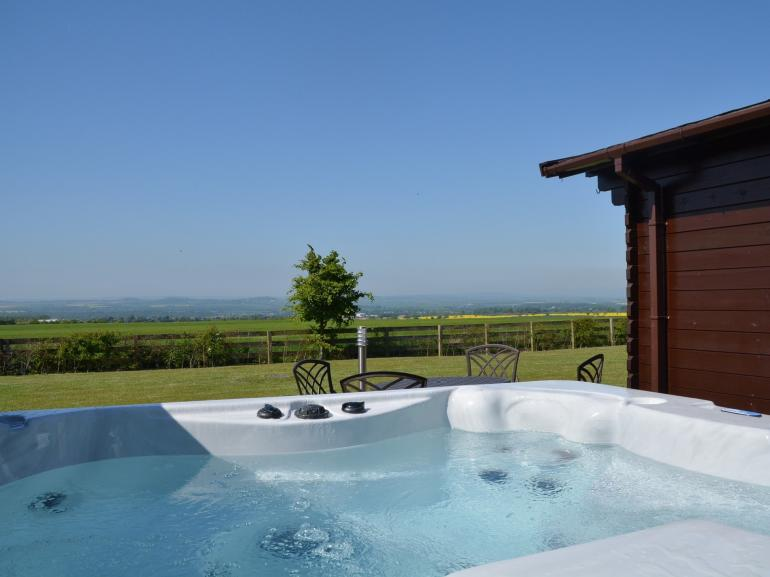 Relax and enjoy a dip in the lovely hot tub and admire the views