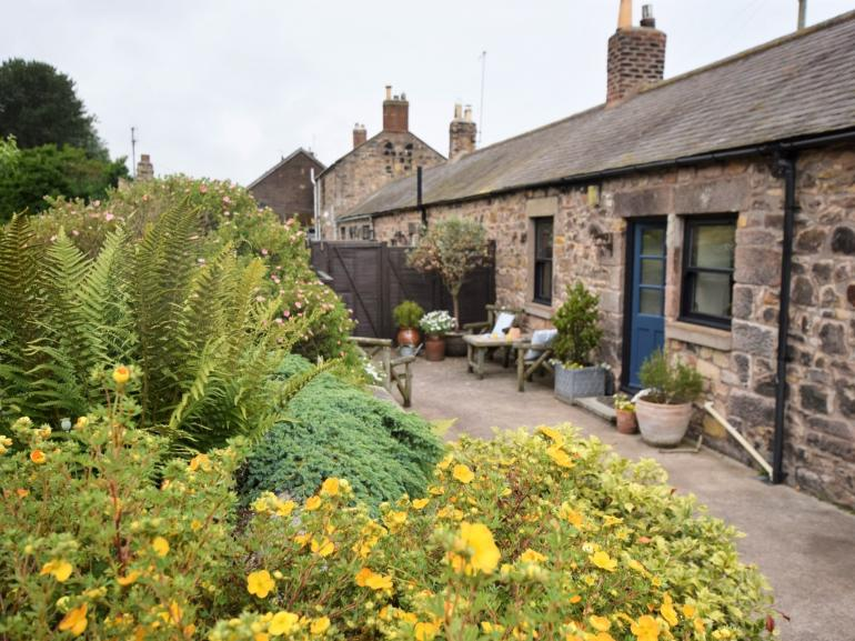 This gorgeous cottage is surrounded by colourful gardens
