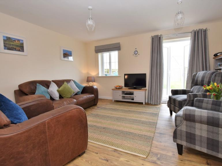Cosy lounge with patio doors to the garden and a short walk to the beach