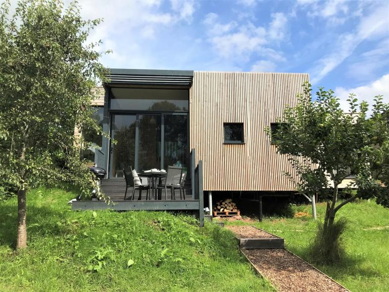 A stunning eco friendly lodge set in a streamside orchard with hot tub