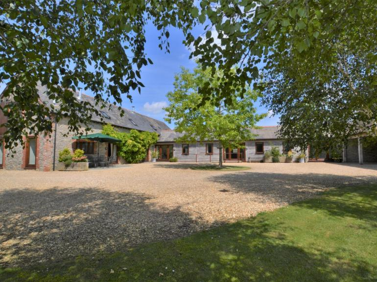 View towards the property nestled in a pretty gravelled courtyard setting