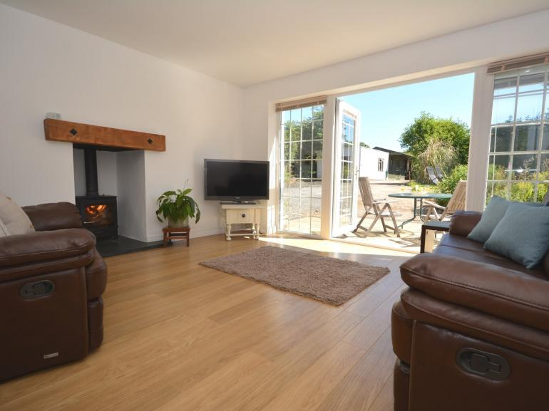Lovely spacious lounge with warming wood burner and patio doors to the garden