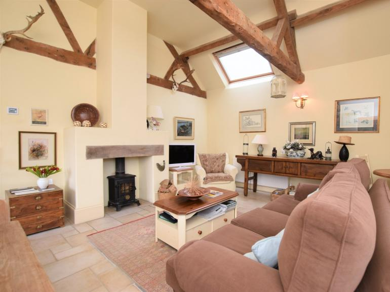 Attractive open plan space with vaulted beamed ceiling and wood burner