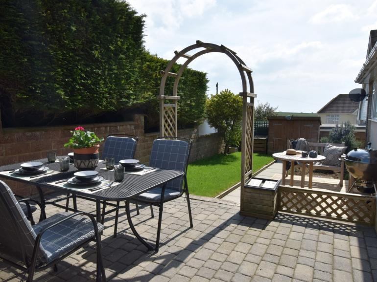Pretty secluded garden for dining al fresco in this seaside cottage