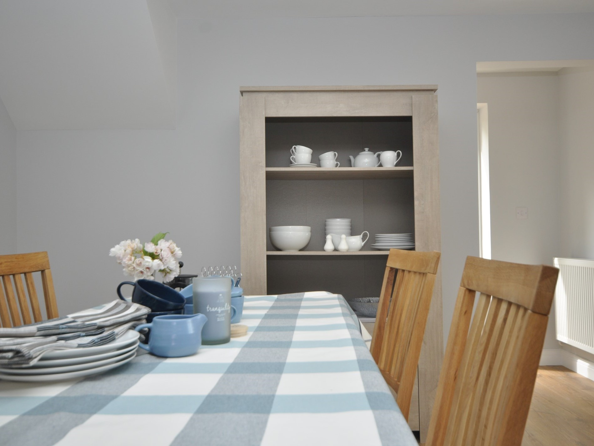 The open dresser is well stocked with simple white china