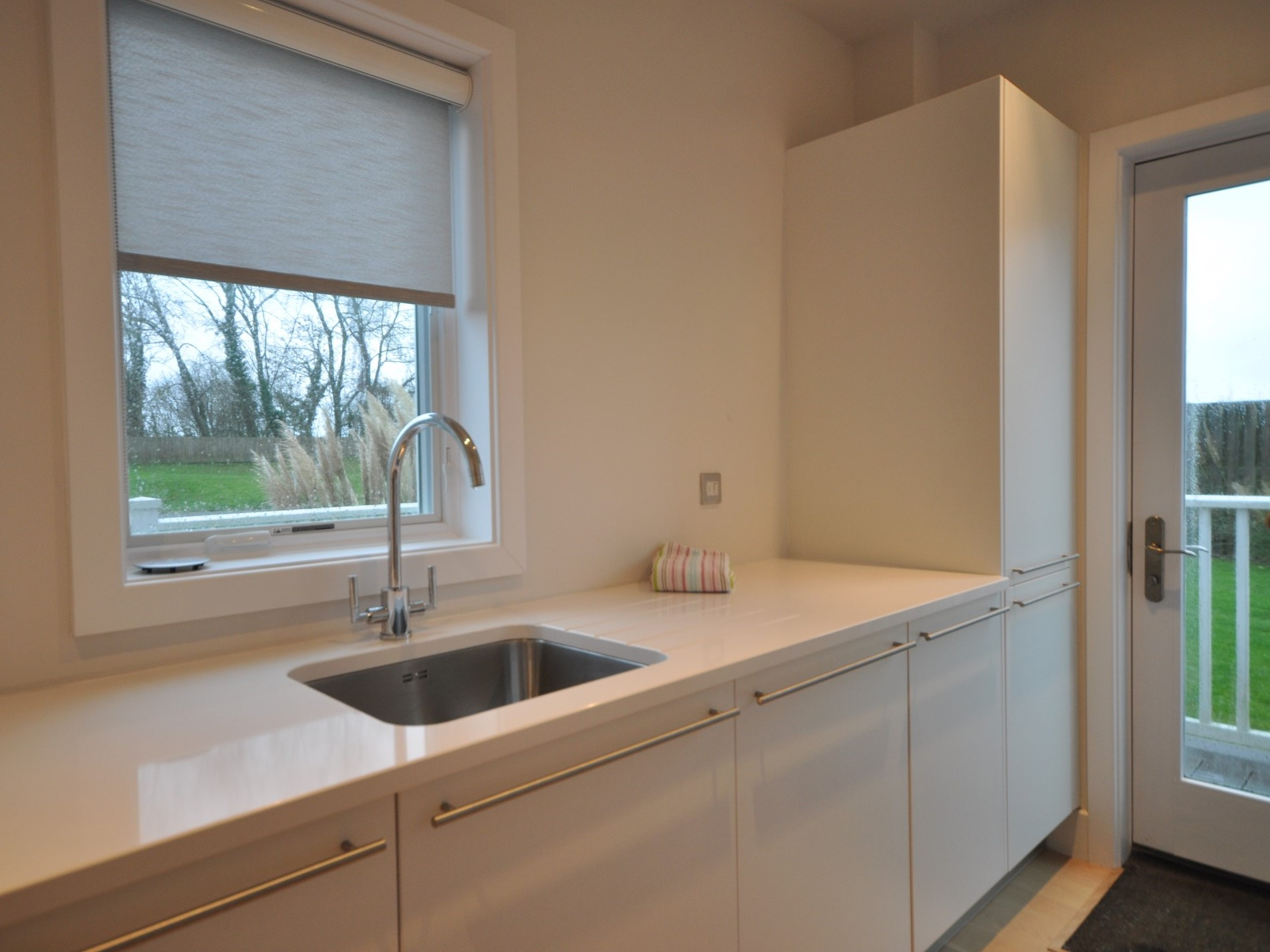 A utility room with additional storage and washing machine