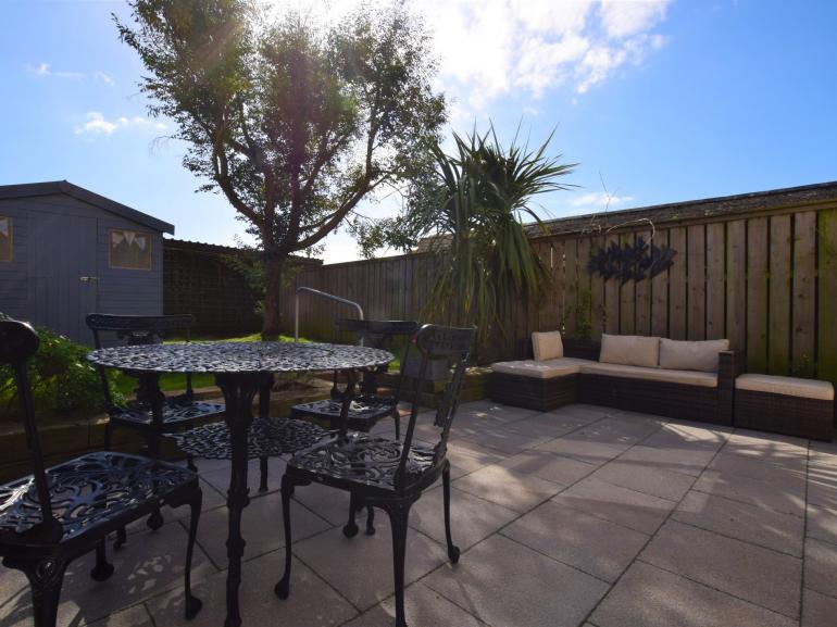 Enjoy al fresco dining in this enclosed rear garden area