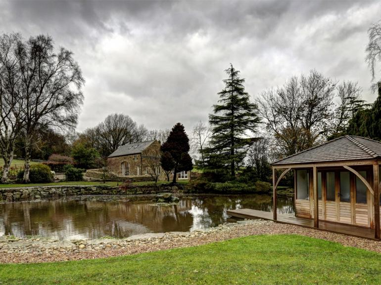 A private pond and summer house are located within the owner's grounds in front of the property