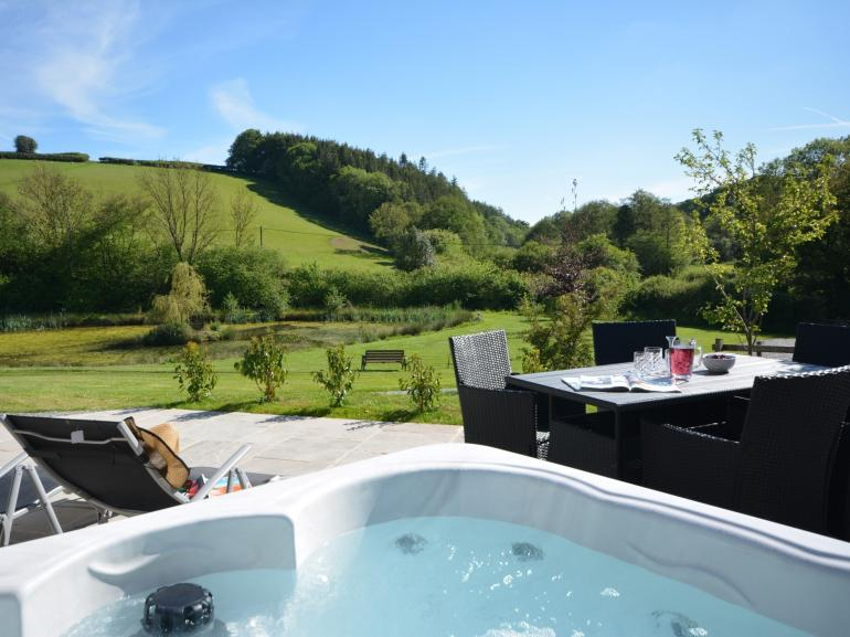 Step outside and enjoy the hot tub and surrounding scenery