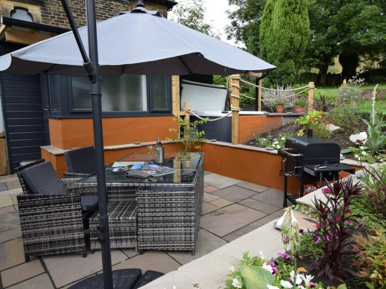 The patio area is complete with comfortable seating and a BBQ