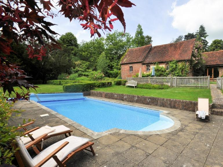View across the pool to the converted coach house