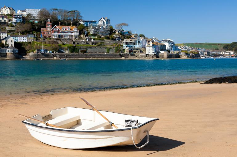 Rowboat on a beach with azure water behind