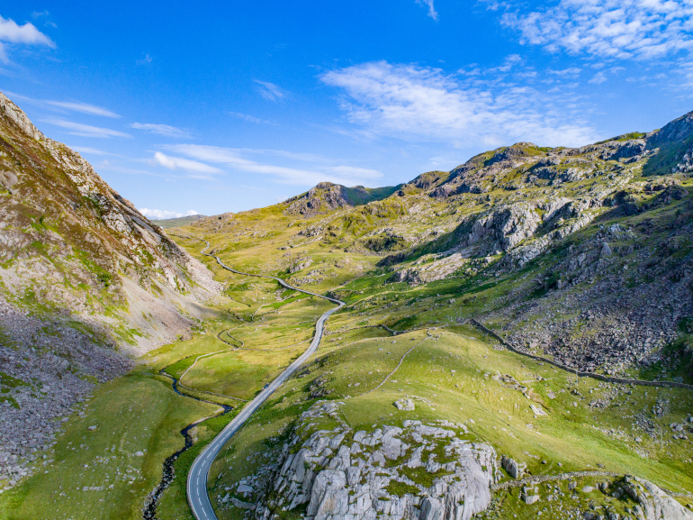 A road winding through the mountains of Snowdonia National Park, Wales