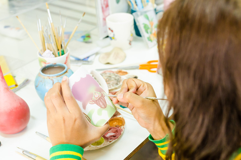 Girl painting a pot at Little Gems on a rainy day in Sussex