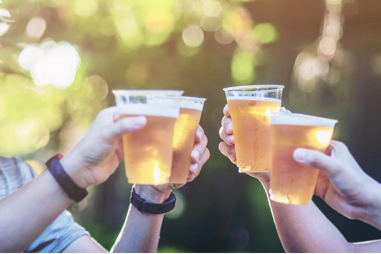 Four people holding up pints of beer in plastic cups