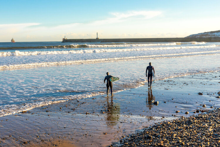 Surfers taking on the waves on Aberdeen Beach