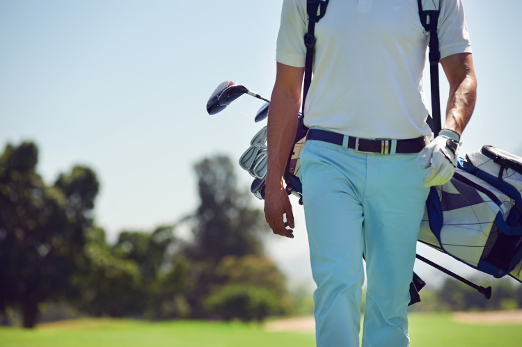 golfer walking across green with bag of golf clubs