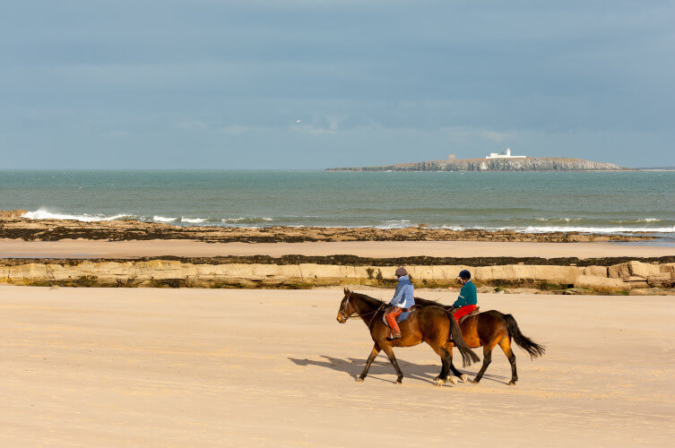 Horse riding on Bamburgh beach near Seahouses in Northumberland