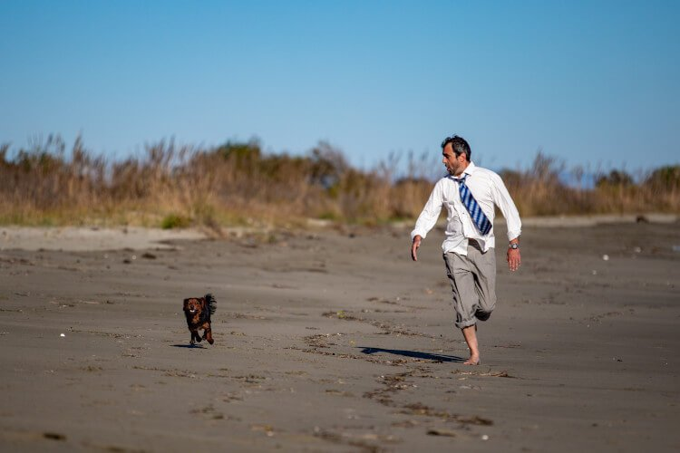 Man in suit on beach with dog