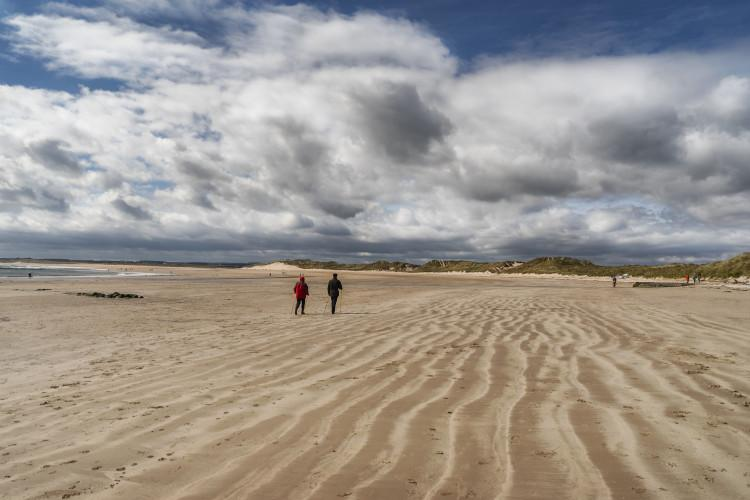 Couple walking on Beadnell Beach Northumberland