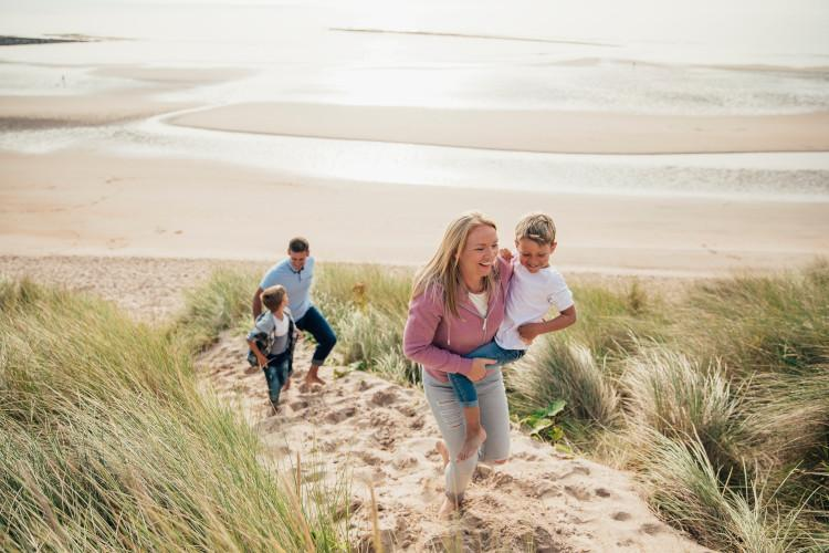 Family running through the sand dunes