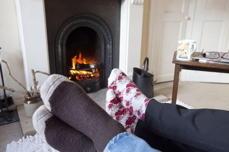 Feet in front of woodburning fire