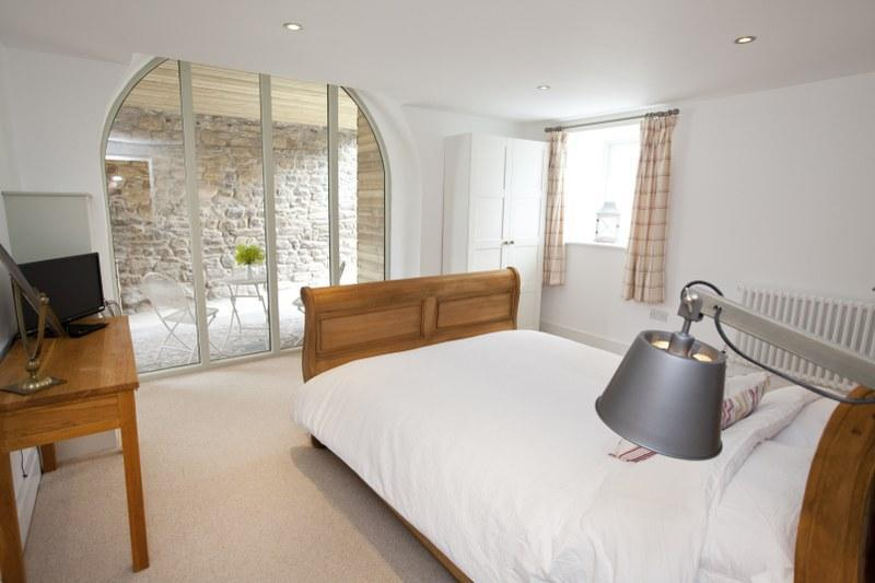 The first of two stunning bedrooms, this ones on the ground floor and boasts a gorgeous floor to ceiling arched window.