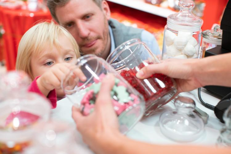 Child choosing sweets with her father