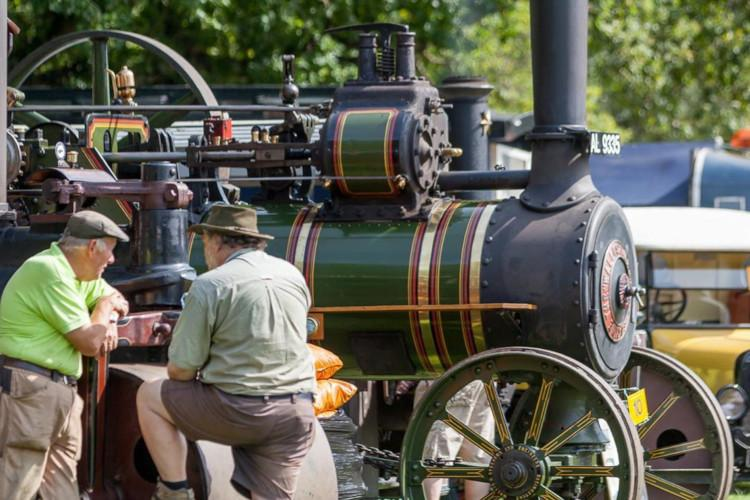 men sitting in front of steam train