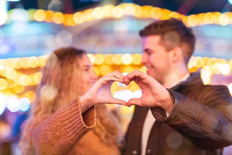 couple making heart at fair